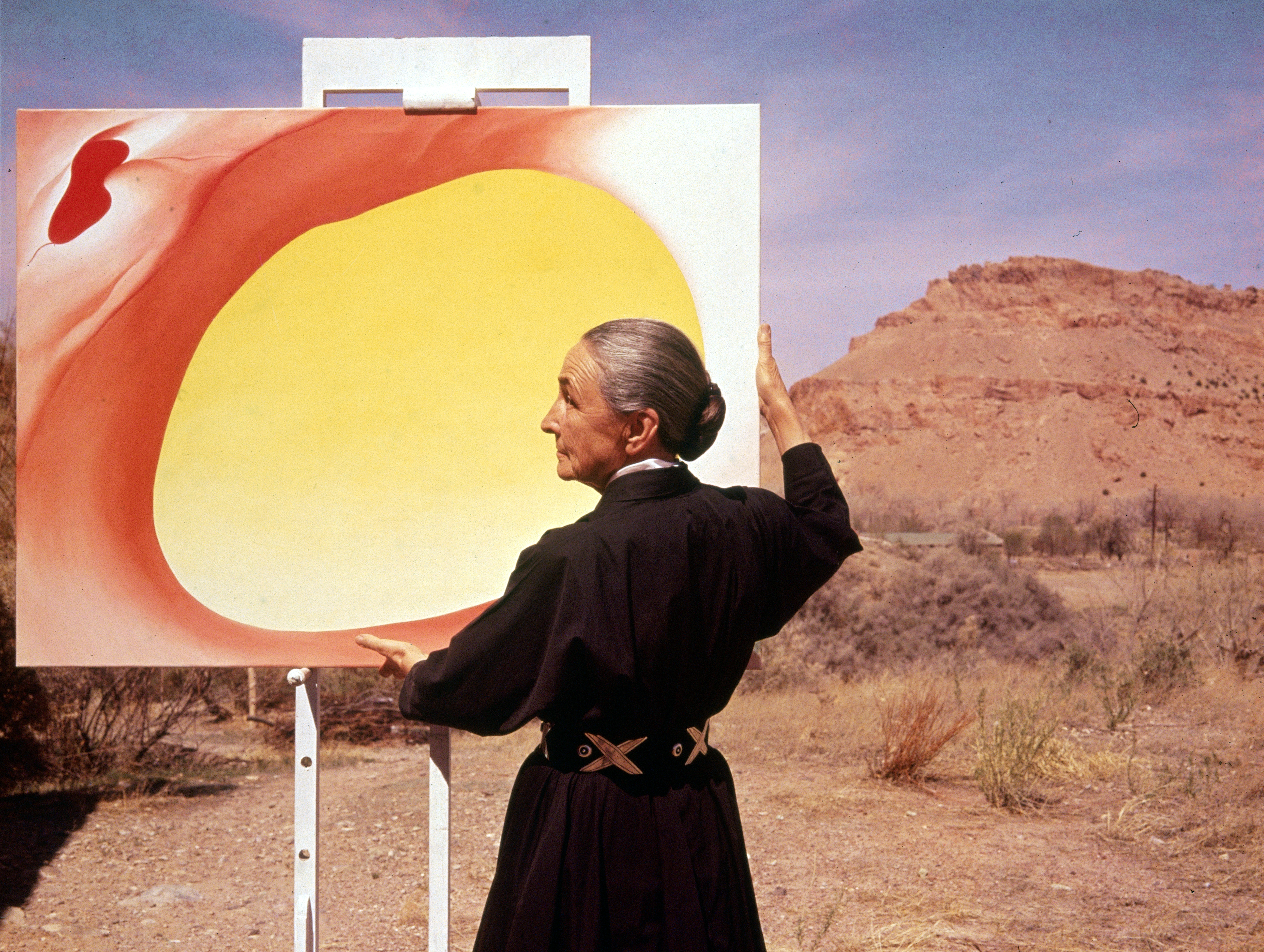 """American artist Georgia O'Keeffe (1887 - 1986) stands at an easel outdoors, adjusting a canvas from her """"Pelvis Series- Red With Yellow,"""" Albuquerque, New Mexico, 1960"""